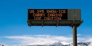 Image of electronic road sign, warning motorists of ice and snow conditions ahead.